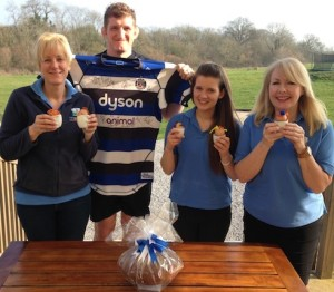 Bath Rugby players paint eggs for farm shop Easter fundraiser, for Dorothy House. From left to right: Liz Nelson, co-owner of Farleigh Road Farm Shop & Café; Stuart Hooper, captain of Bath Rugby; Rebecca Wright and Anne Priest, eggcited café staff