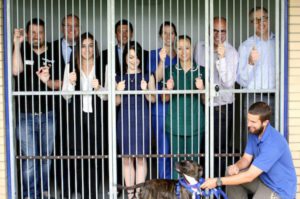 Lola and her carer Ben keep an eye on Kennel Break fundraisers. From left to right: Kevin Ravelin, Bath Cats & Dogs Home; Steve Smitherman, Barclays; Rebecca Land from Systemagic; Nick Raine from Novia; Natalie Giles, Zest; Gwen Cardiff and Tracey Farion from Bath Vets; Andrew Paull and Brian Topper from Centaur